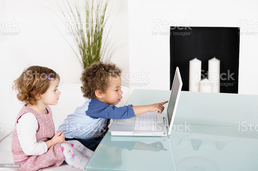 Little Girl and Boy Reviewing Something On The Laptop royalty-free stock photo