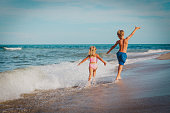 little girl and boy run fly play with waves on beach vacation