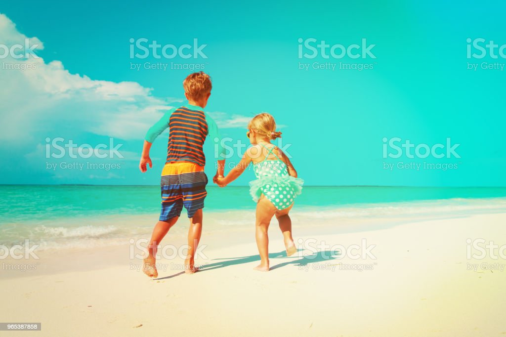 little girl and boy run play with water on beach royalty-free stock photo