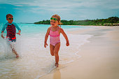 little girl and boy run play with waves on beach vacation