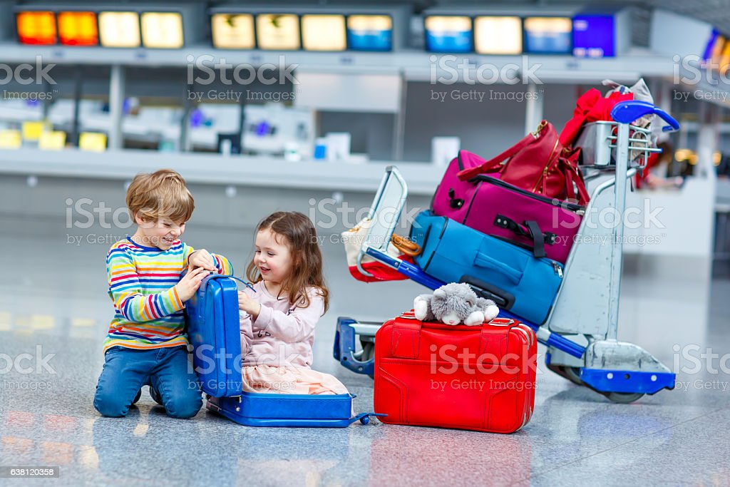 Little girl and boy sitting on suitcases on airport stock photo