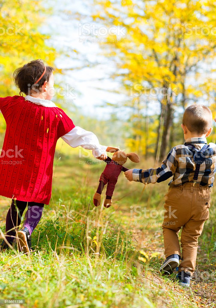 Little girl and boy walking with their favorite toy stock photo