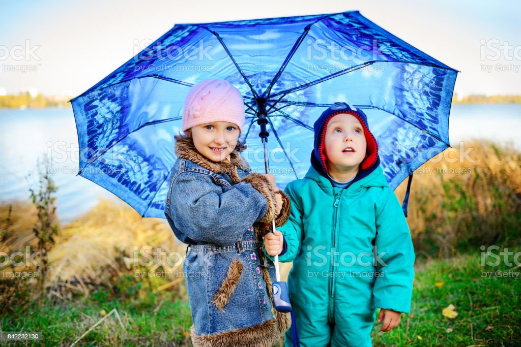 Little girl and boy with umbrella playing in the rain. Kids play outdoor by rainy weather in fall. Autumn fun for children. Toddler kid in raincoat and boots walk in the garden. stock photo