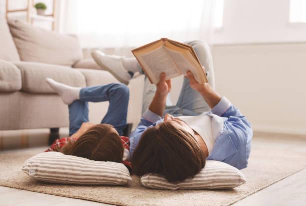 Kleines Mädchen und Vater genießen Buch zusammen, auf dem Boden liegend – Foto