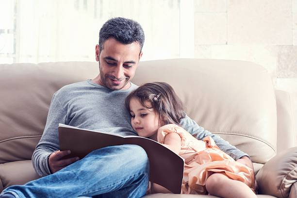 little girl and father reading book together - famille monoparentale photos et images de collection