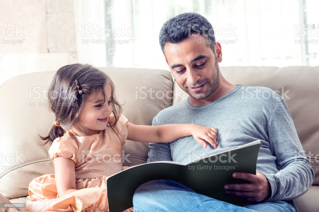 Little Girl And Father Reading Book Together stock photo
