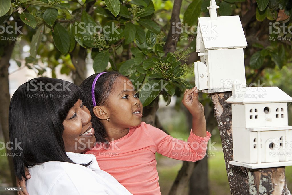 Little girl and grandmother playing with birdhouse royalty-free stock photo