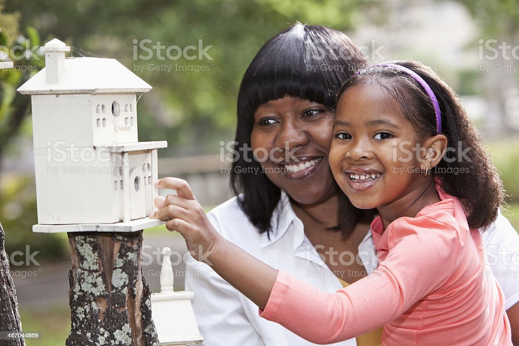 Little girl and grandmother playing with birdhouse stock photo