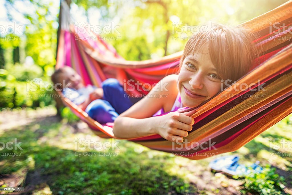 Little girl and her brother playing on hammock stock photo