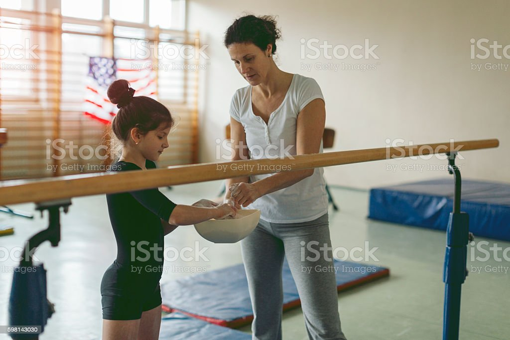 Little girl with her coach and mother applying sports chalk onto...