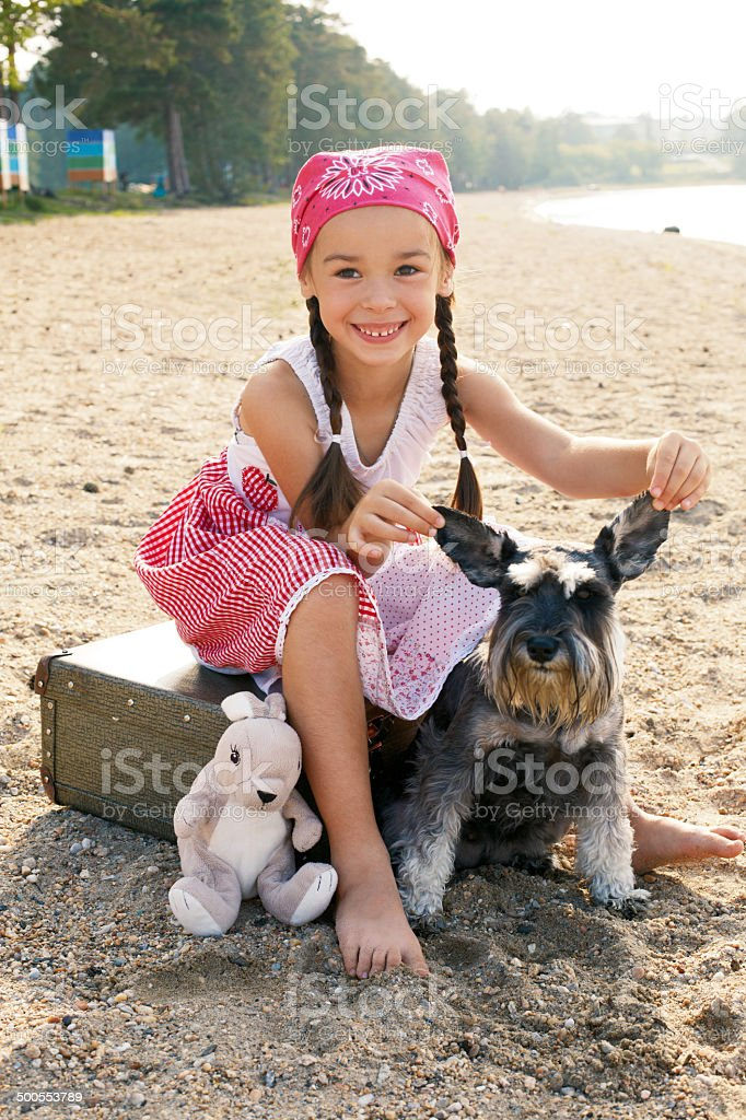 little girl and her dog sitting on the bank stock photo