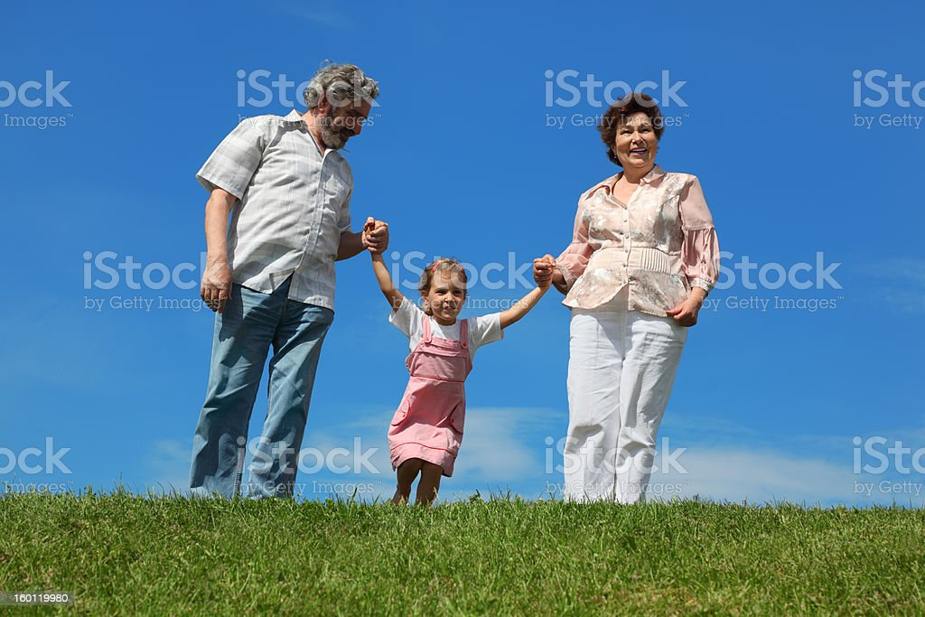 Little girl and her grandparents standing on lawn royalty-free stock photo