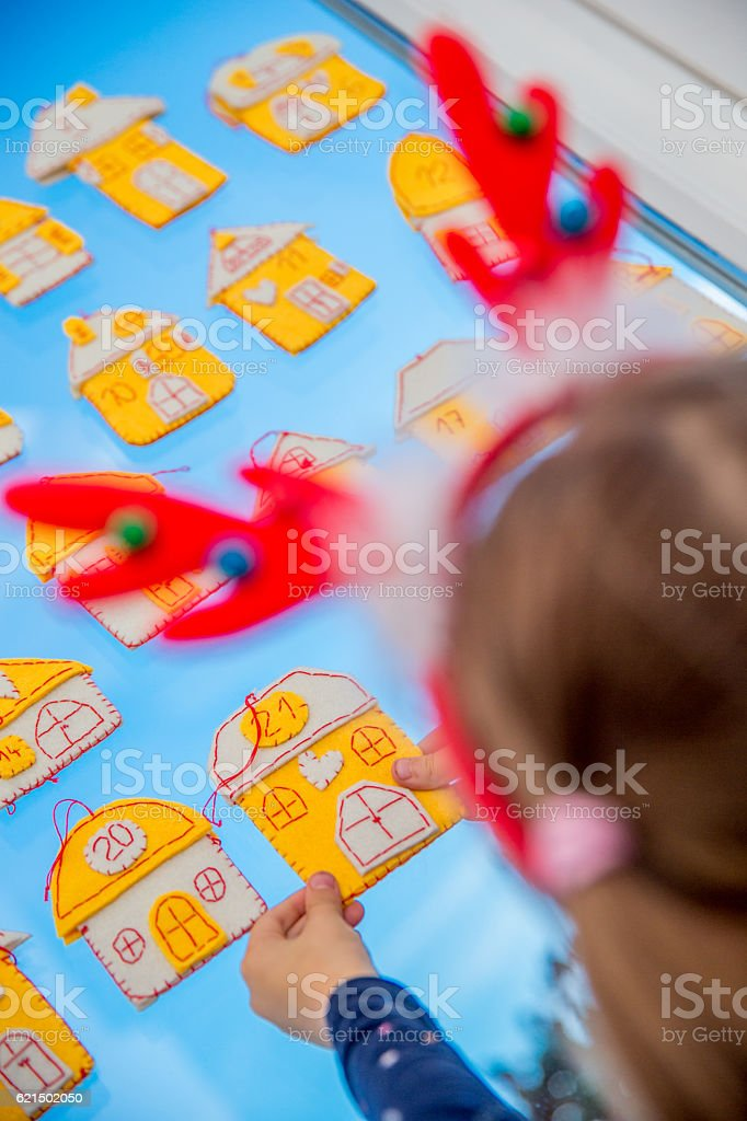 Little Girl and her Homemade Advent Calendar on Window foto stock royalty-free