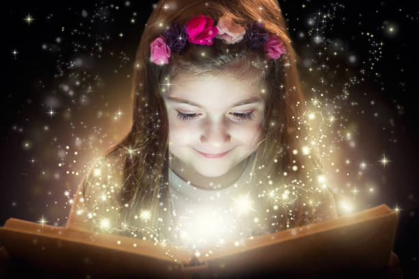 little girl and her magic book - fairy wand stock photos and pictures
