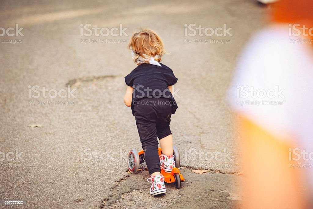 Little girl and her mom playing in the park with the push scooter. stock photo