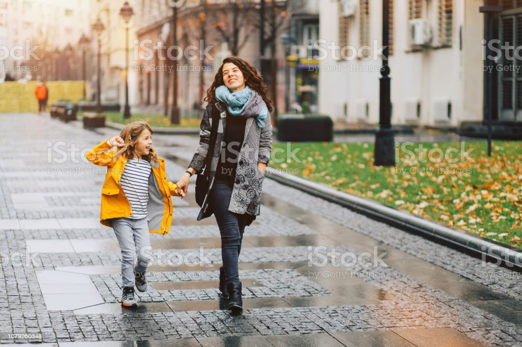 Little girl and her mom walking through the city stock photo
