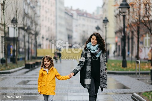 Young girl walking on the street with her mom. They're having a fun time together, spending time on the empty streets of the Sunday morning.