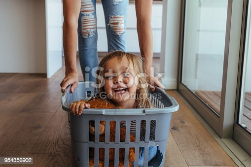 954356678 istock photo Little girl and her mother having fun doing laundry 954356902