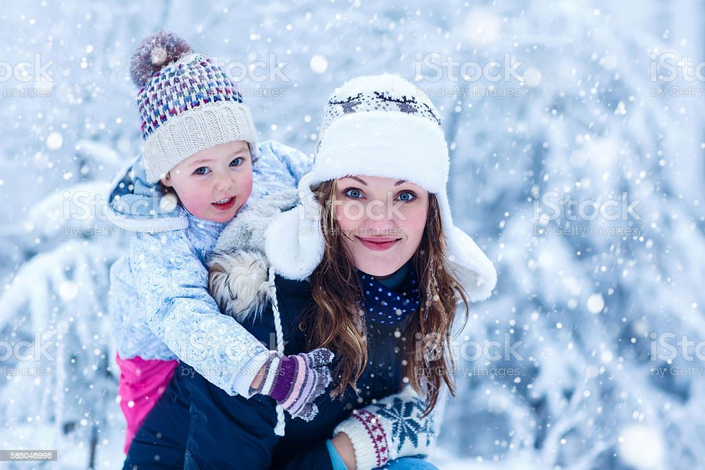 little girl and her mother in winter forest with snow stock photo