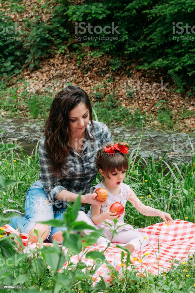 A little girl and her mother on a picnic in the nature foto de stock royalty-free