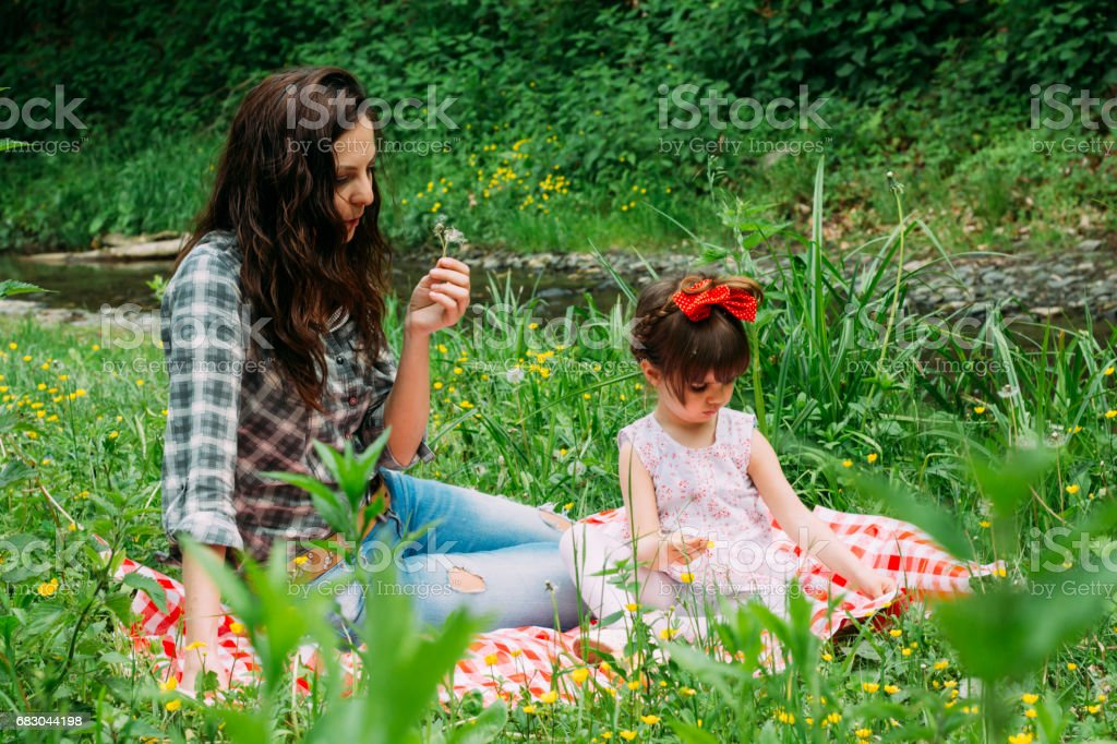 A little girl and her mother on a picnic in the nature royalty-free stock photo