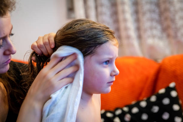 little girl and her mother young mother is drying her daughter's hair using a towel wet hair stock pictures, royalty-free photos & images