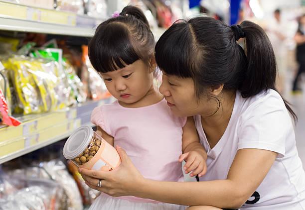 kleine mädchen und ihre mutter einkaufen - pengpeng stock-fotos und bilder