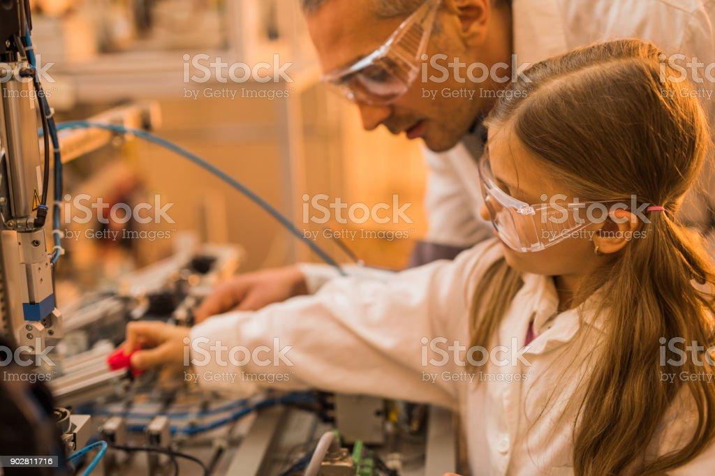 Niña y su maestro trabajando en maquinaria en laboratorio. - Foto de stock de Adulto libre de derechos