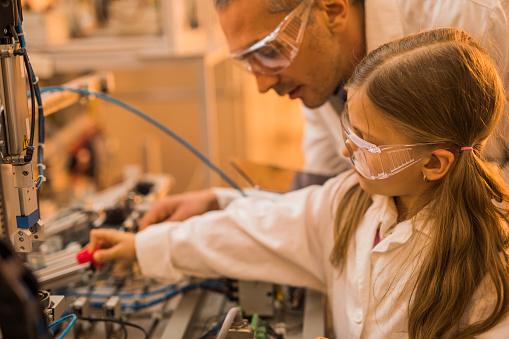 Niña Y Su Maestro Trabajando En Maquinaria En Laboratorio Foto de stock y más banco de imágenes de Adulto