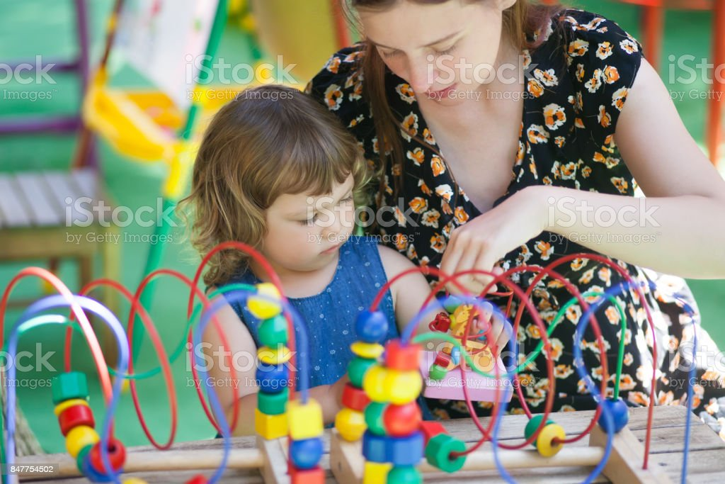 Little girl and mother playing with educational toy. stock photo