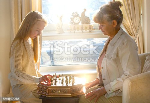 istock Little girl and pension age woman playing playing chess in the domestic environment. People agains sun light. Educational concept 876542018