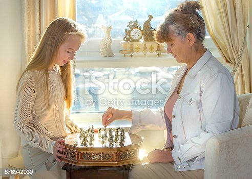 istock Little girl and pension age woman playing playing chess in the domestic environment. People agains sun light. Educational concept 876542030
