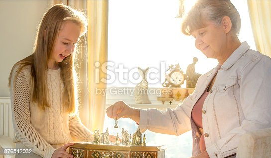 istock Little girl and pension age woman playing playing chess in the domestic environment. People agains sun light. Educational concept 876542032