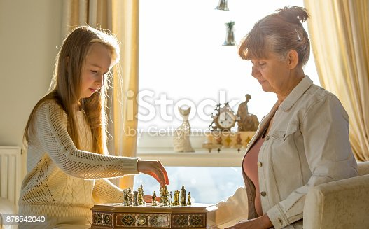 istock Little girl and pension age woman playing playing chess in the domestic environment. People agains sun light. Educational concept 876542040