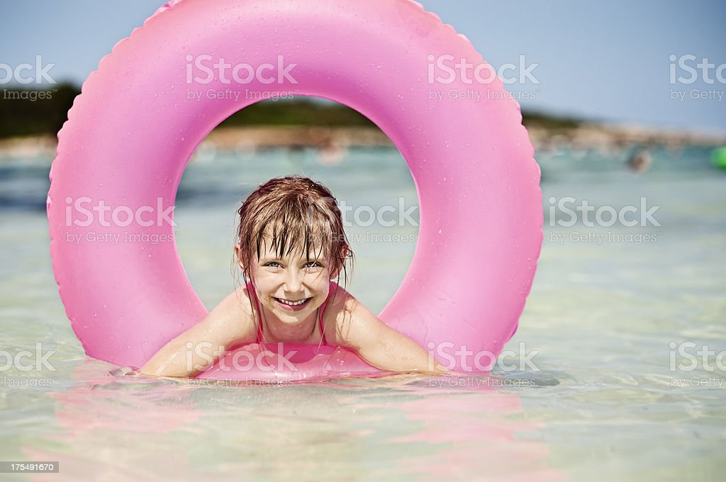 Little girl and pink swimming tube in sea. royalty-free stock photo