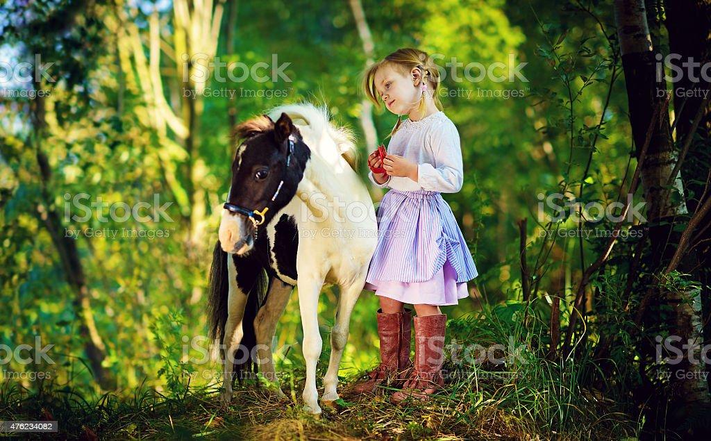 Little girl and tiny pony stock photo
