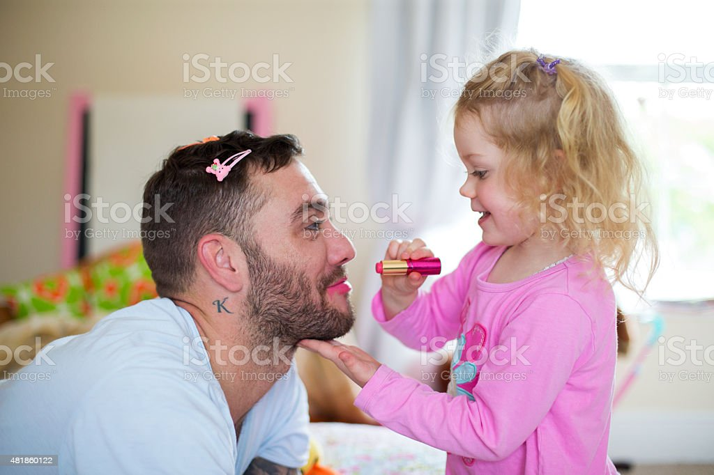 Little Girl Applying Make-up to her Daddy. stock photo