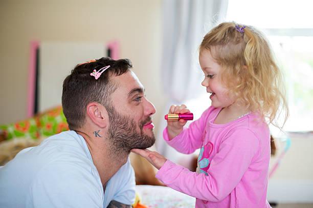 kleines mädchen, die anwendung von make-up zur ihr daddy. - papa humor stock-fotos und bilder