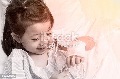 istock Little Girl Asia Hand of the sick child with saline solution. 697299602