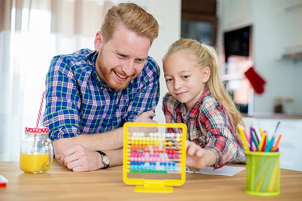 little girl asks for dads help with homework - innocent saft stock-fotos und bilder