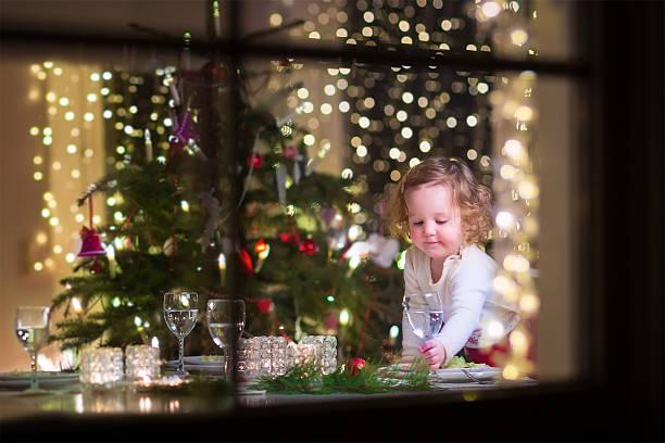 kleines mädchen im weihnachts-abendessen - kinderzimmer tischleuchten stock-fotos und bilder