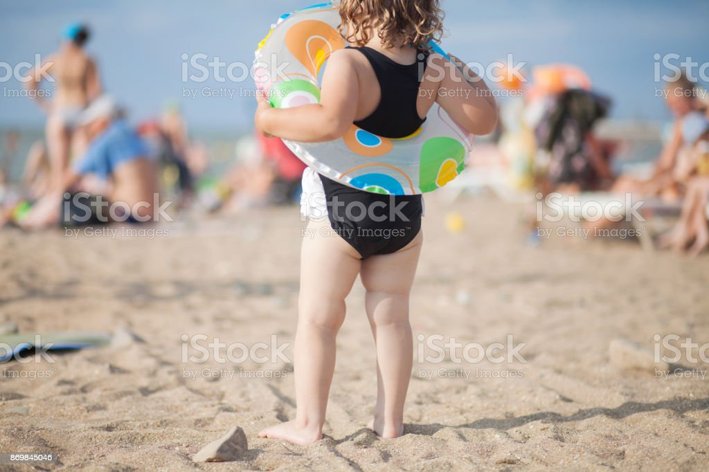 Little girl at hge beach, crowd on the background. stock photo