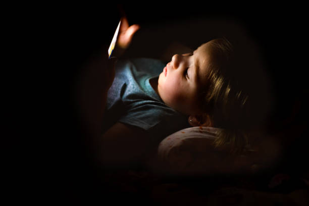 Little girl at home at night watching something on smartphone. stock photo