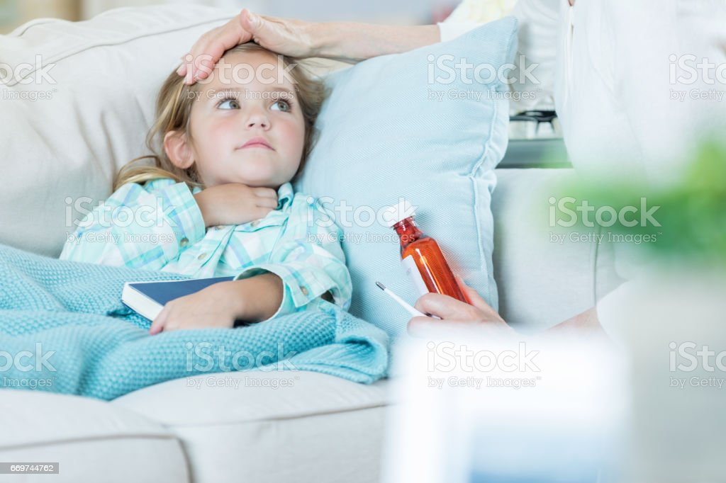 Little girl at home sick stock photo