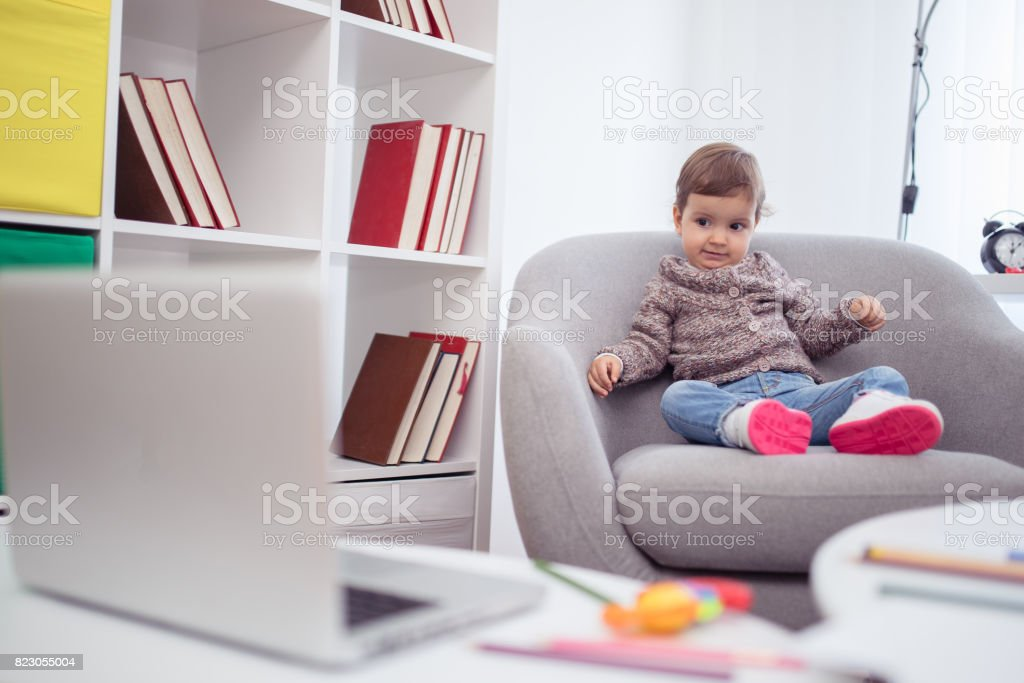 Little girl at home watching cartoons stock photo