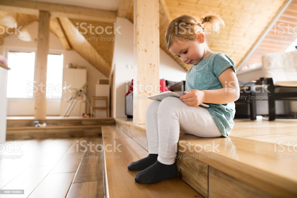Little girl at home watching something on tablet. stock photo