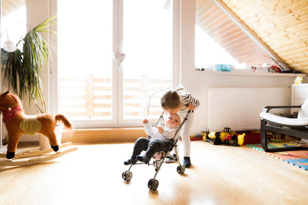 Little girl at home with baby brother in toy stroller. stock photo