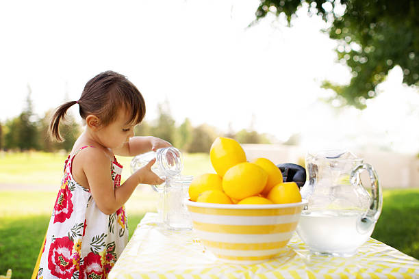 Little Girl At The Lemonade Stand Little Girl At The Lemonade Stand Transferring Lemonade From One Cup to Another Outdoor in A Summer Day. lemonade stand stock pictures, royalty-free photos & images