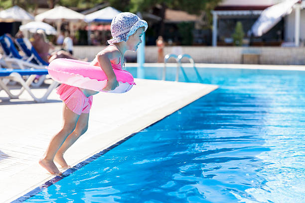 Royalty Free Cute Little Girl Jumping Into Swimming Pool Pictures Images And Stock Photos Istock