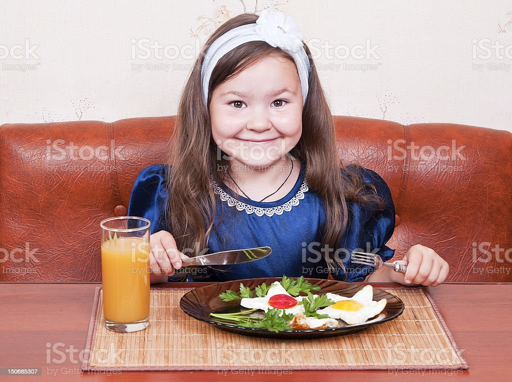 Little girl at the table, eating scrambled eggs royalty-free stock photo